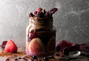 Aufgehübschtes Glas mit Beeren-Chiapudding, Schoko-Nicecream und Früchten
