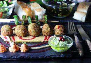 Mezze! Falafel mit Baba Ganoush Kern auf Hummus Bett, Muhammara, Granatapfelsauce, Grüner Tahini-Sauce, Knoblauch-Oliven, Salat und gegrillter Zucchini