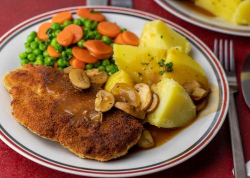 Schnitzel, Kartoffeln, Sauce, Erbsen, Möhren