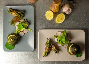 Grüne Bohnen im Speckmantel an gefüllten runden Zucchini