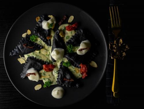 Schwarze Ricotta-Tomaten-Ravioli auf Petersiliensauce