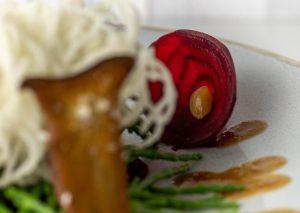 Haudünne Rote Beete Scheibe mit kleiner fermentierter Knoblauchzehe