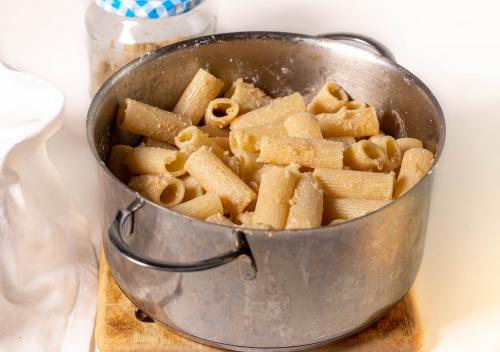 Die Pasta al dente kochen, dann in Macadamia Parmesan wenden