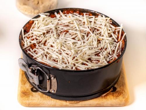 Mit reichlich Bolognese übergießen und mit veganem Käse bestreuen