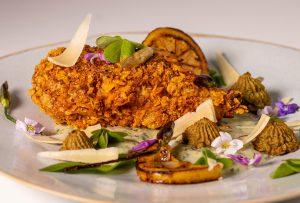 Krosse Cornflakespanade mit Röstzwiebeln um ein veganes Hähnchenbein