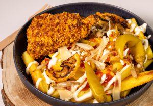 Fast Food mit Loaded Fries und panierten Hähnchenkeulen, vegan